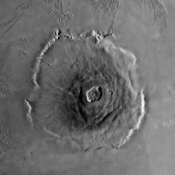 Olympus Mons, a shield volcano, is the tallest volcano in the solar system. It rises 27 kilometers (17 miles) high, spreads over 600 km (370 mi) at the base, and is surrounded by a well-defined scarp that is up to 6 km (4 mi) high. Lava flows drape over the scarp in places. Much of the plains around the volcano are covered by ridged and grooved terrain called the aureole. The origin of the aureole is controversial, but may be related to material sliding off of the flanks of an ancestral volcano. The summit