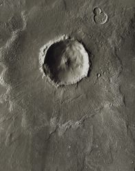 Bacolor Crater is about 20 kilometers (12 miles) wide. Note how the outer edge of the ejecta blanket has a raised rim, or rampart. This is where the outward flow came to an abrupt halt and material piled up behind it. Bacolor also shows lines on the ejecta blanket. These came from a surge of superheated gas and debris flying outward following the impact. (NASA/JPL-Caltech/Arizona State University)
