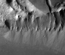 Streams flowing over the edge of Kasei Valles (top) washed down sediments that collected as alluvial fans at the foot of the slope. (NASA/JPL-Caltech/Arizona State University)