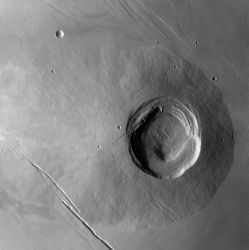 Biblis Patera (now called Biblis Tholus) is a small shield volcano in Tharsis. Its flanks are steep and composed of basaltic lava. Its gaping caldera — what is now identified as Biblis Patera — shows several concentric rings, which point to multiple episodes of lava collapse. Younger smooth volcanic plains surround the volcano and hide its probable true size. What we can see of it is about 170 kilometers (105 miles) wide. (NASA)