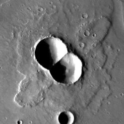 "Doublet craters such as this form by the simultaneous impact of a meteor that broke in two pieces prior to hitting the surface. The ejected debris shoots out to the sides forming the ""wings."" This doublet lies in Utopia Planitia, near the Elysium volcanic region. (NASA/JPL-Caltech/Arizona State University)"