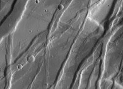 A graben is usually a small-scale tectonic feature, where the ground between two faults drops down. (If the ground is raised, scientists call it a horst.) Tempe Fossae is a large area on Mars much broken up by grabens. (NASA/JPL-Caltech/Arizona State University)