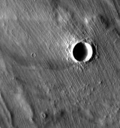 Grooved terrain (interrupted by an impact crater) overlies lava flows near the giant shield volcano Arsia Mons. The parallel ridges may be moraines, deposits of sand and rocks left by a cold-based glacier on the side of the volcano. (NASA/JPL-Caltech/Arizona State University)