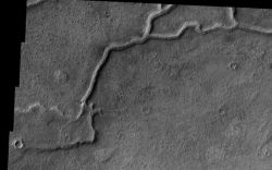 A streams can carry rocks, gravel, and sand in its bed. The same holds when a stream flows under a glacier, but the tunnel in the ice confines the streambed deposits. When the glacier goes away, the deposits remain as a winding ridge geologists call an esker. (NASA/JPL-Caltech/Arizona State University)