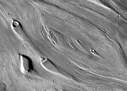 The channel bed of Kasei Valles on Mars shows lineations that formed when the floodwaters carried giant rocks and boulders downstream (upper left to lower right). The floods also eroded smooth streamlines around hills and raised features, such as the crater at upper left. Note: light is coming from the left. (NASA/JPL-Caltech/ASU)