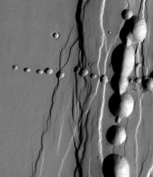 Pit craters often form on volcanoes. Some occur along fractures and faults, others along subsurface lava channels called lava tubes. After the lava drains away, parts of a lava tube's roof will collapse under its own weight. This image shows fracture-related pits running north-south, and an east-west set of pits that probably track an underground lava tube. (NASA/JPL-Caltech/Arizona State University)