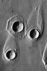 Floodwaters surged through Maja Valles (from bottom toward top in the image). The floods were forced to detour around two craters because they were surrounded and armored by the rocky debris thrown out in the impacts. The diverted floodwaters left streamlined hills behind the craters. Then a third meteorite impacted. It shows what the other two probably looked like when freshly made — but because the floods had ended, the third crater stands almost unchanged. (NASA/JPL-Caltech/Arizona State University)